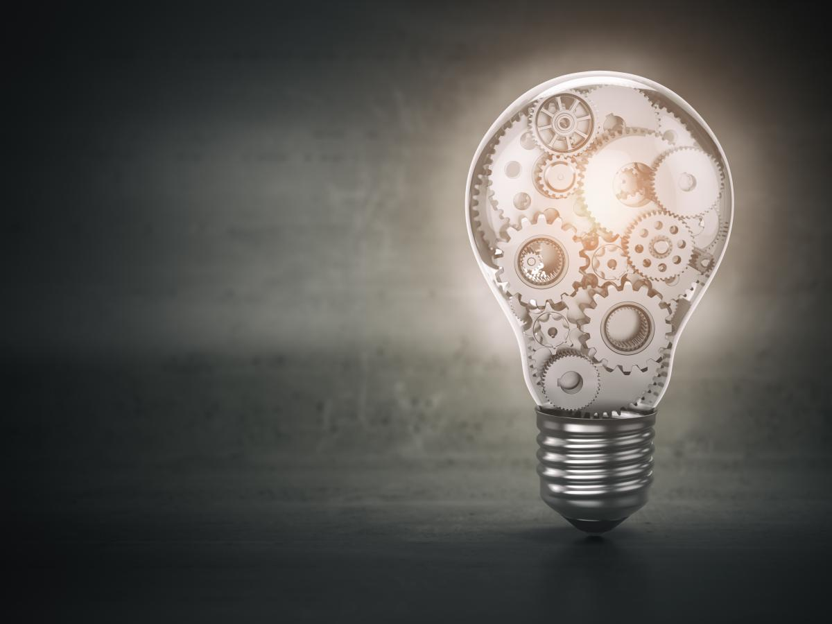 black background with lightbulb filled with interlocking gears