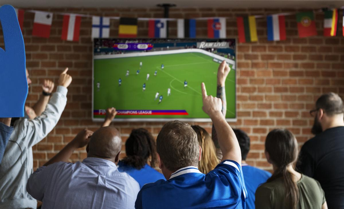 group of people watching the world cup on television