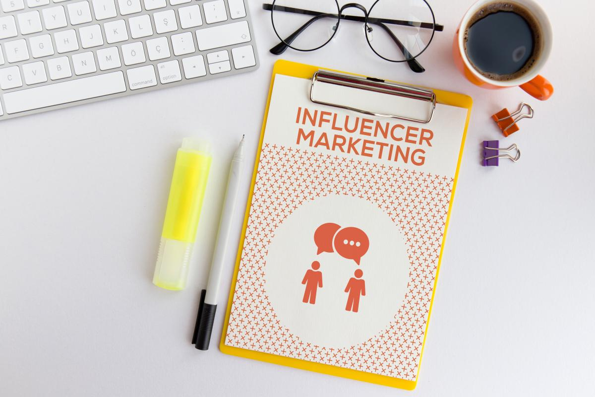 a note next to a keyboard reads influencer marketing