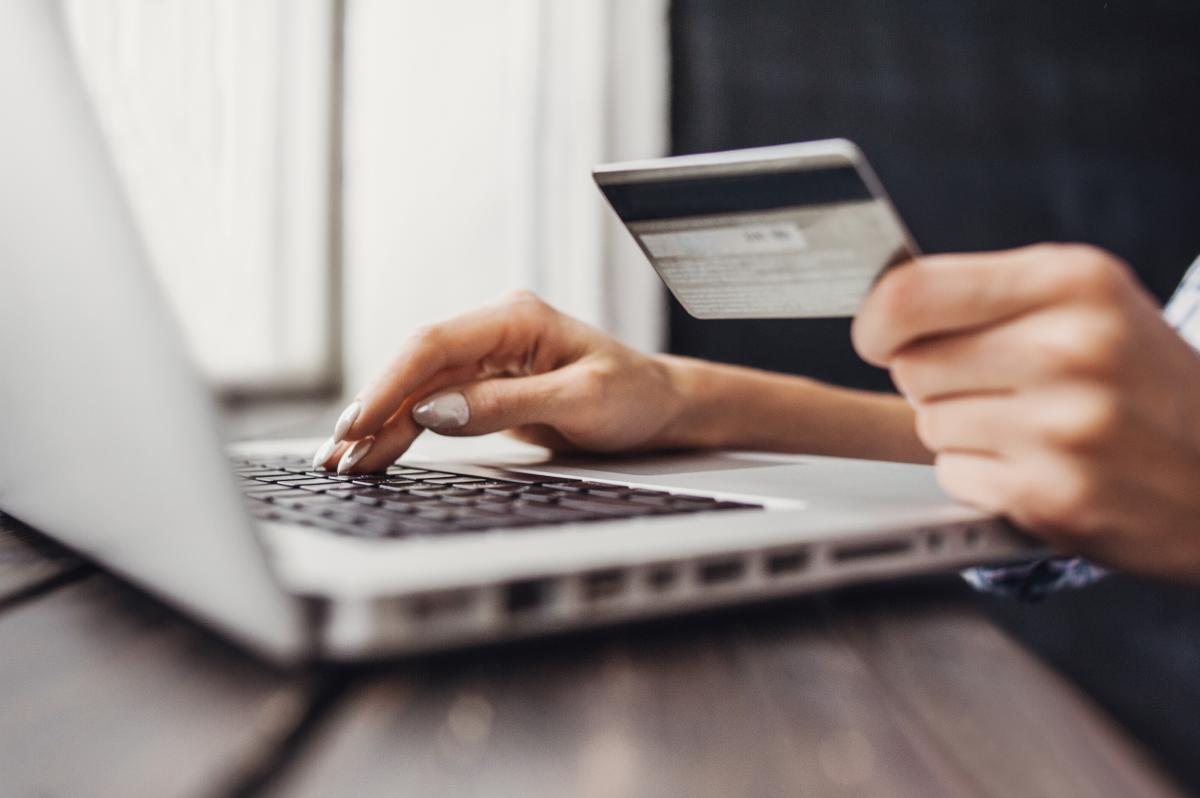 online shopper types at keyboard with credit card in hand