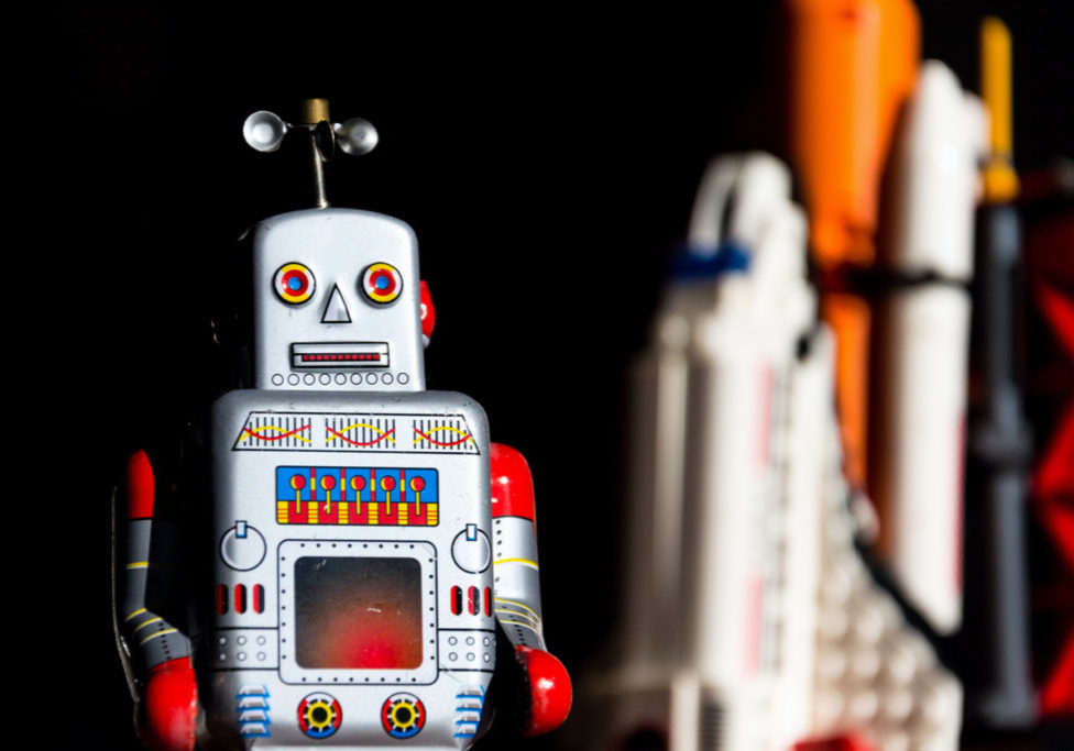 Vintage tin toy robot looking into the future of space exploration with rocket in background, artificial intelligence and space tourism concept