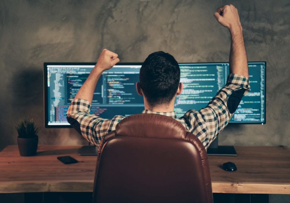 Rear back behind view of brunet guy wearing checked shirt professional expert, sitting in front of screen celebrating accomplishment at wooden industrial interior work place station