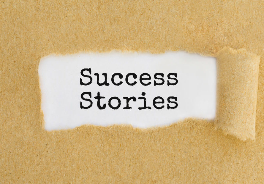 Text Success Stories appearing behind ripped brown paper