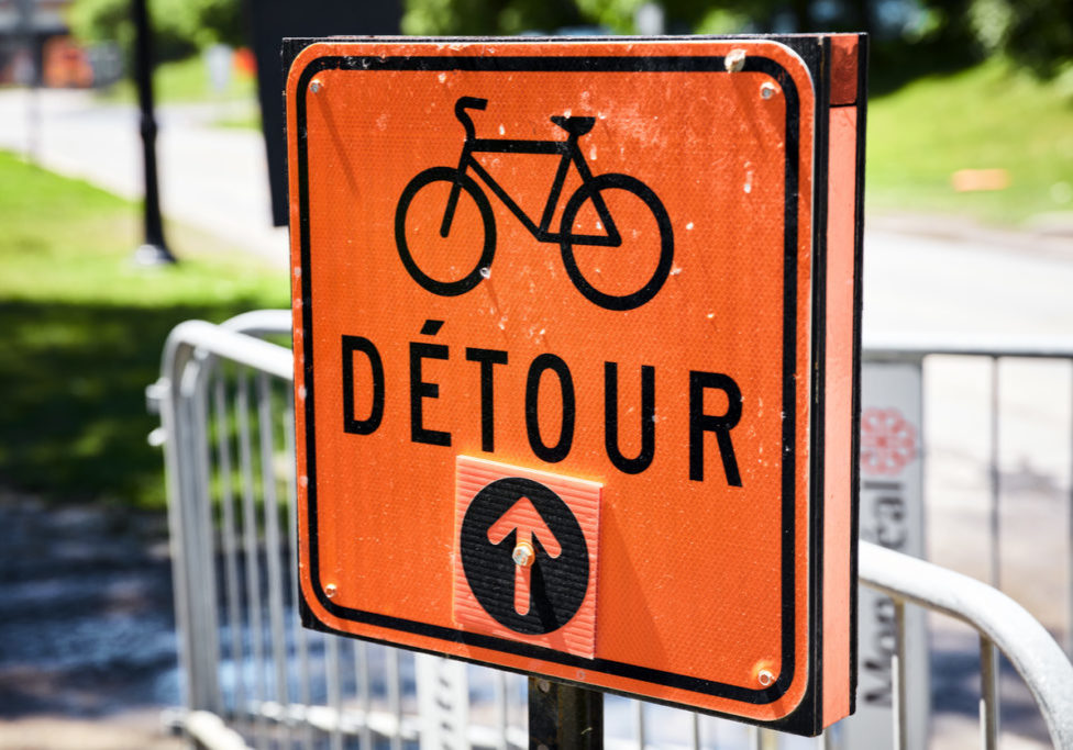 Orange road detour sign for bicycle in French. Arrow pointing straight.